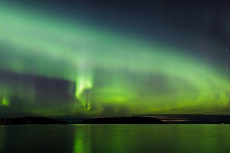 Aurora boreale incandescente sul lago in Finlandia