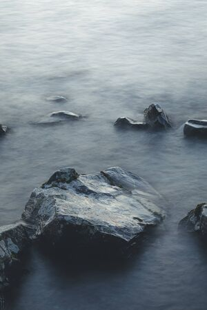 Abstract long exposure of waves and rocks in lake shore at dawn