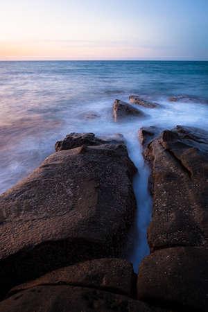 Waves and rocks shore long exposure photo