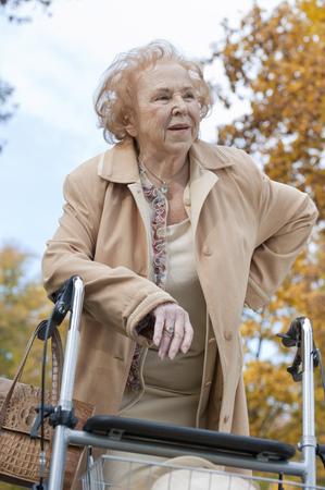 Senior woman leaning on walking frame in park