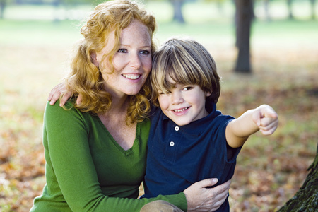Mother and boy in autumn forest LANG_EVOIMAGES