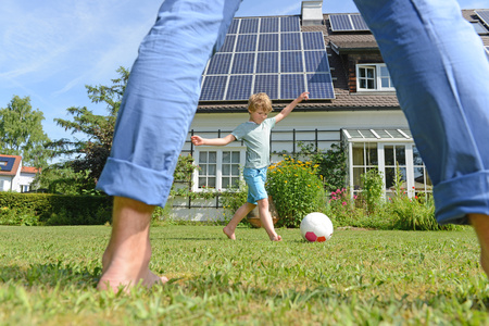 Father and son playing football in garden of solar paneled house