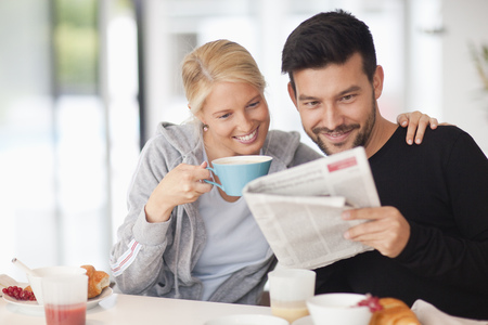 Couple reading newspaper at breakfast, smiling