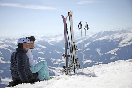 Couple sitting in snow next to skis on mountain