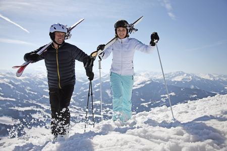 Couple holding skis and walking in snow