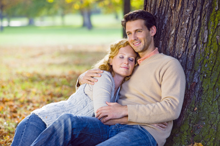 Couple relaxing by tree in autumn forest