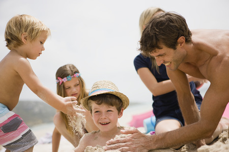 Father burying son on beach, smiling