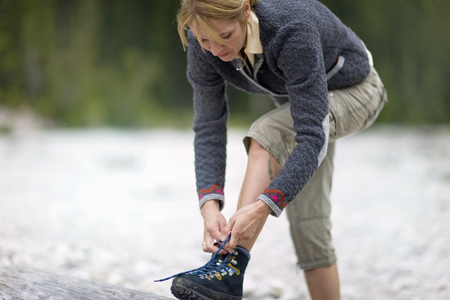 Mature woman tying lace of hiking boot LANG_EVOIMAGES