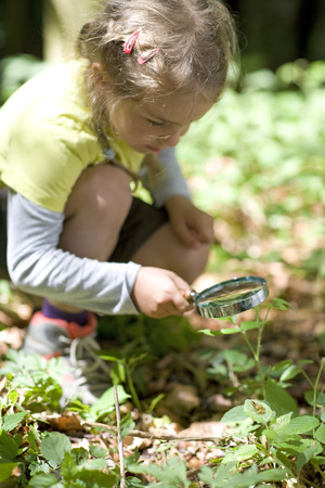 Kindergarten child looking through magnifying glass in a wood kindergarten