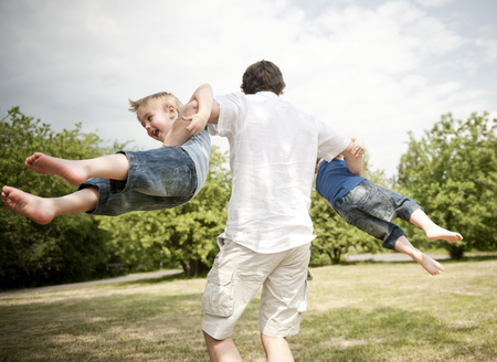 father spinning sons around in park LANG_EVOIMAGES