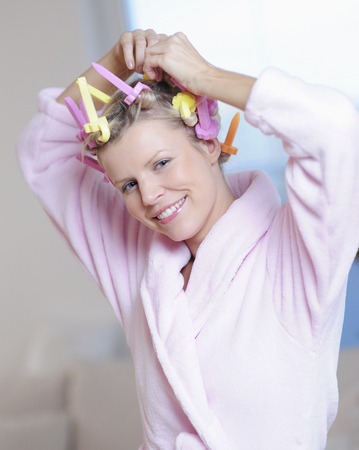 Portrait of young woman with curlers in hair