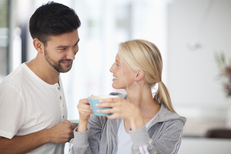 Young woman holding tea cup and smiling at man