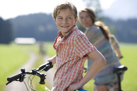 Young boy with bicycle looking over shoulder
