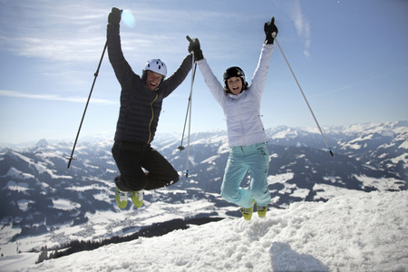Couple jumping in skis on mountain
