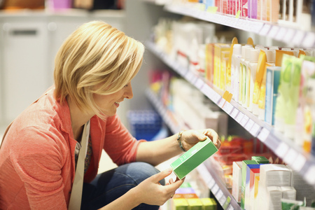 Woman shopping for cosmetics in organic grocery store LANG_EVOIMAGES
