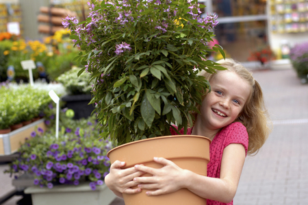 Girl carrying potted plant in garden center
