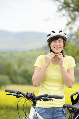 Young woman putting on bicycle helmet LANG_EVOIMAGES
