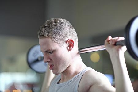 Teenage boy weightlifting in gym LANG_EVOIMAGES