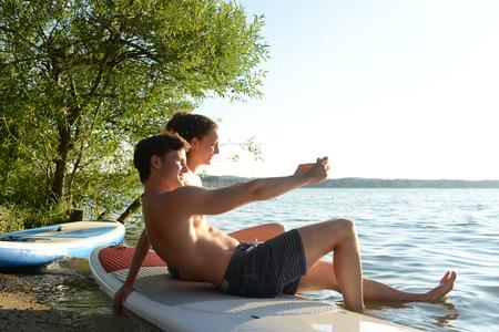 Teenage couple taking selfie on paddleboard, Lake Starnberg, Bavaria, Germany, Europe
