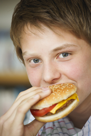 Teenage boy eating cheeseburger