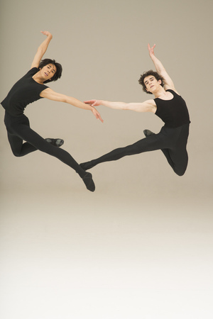 Two young male ballet dancers leaping in the air
