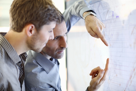 Architect explain plans to colleague in office
