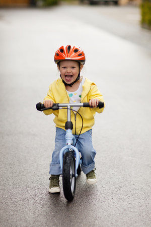 Young happy girl riding bicycle in street with helmet on