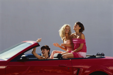 Three girlfriends riding in convertible