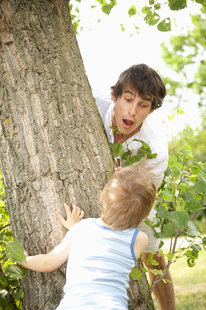 Son surprising father behind tree in park