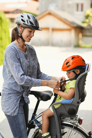 Mother strapping child in car seat on bicycle