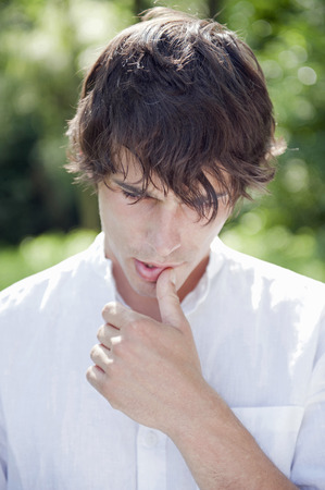 Young man touching lip and looking worried, outdoors