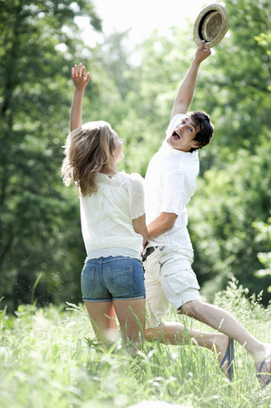 Young couple jumping together in summer meadow