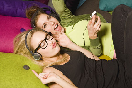 Young women listening to music together on iPod