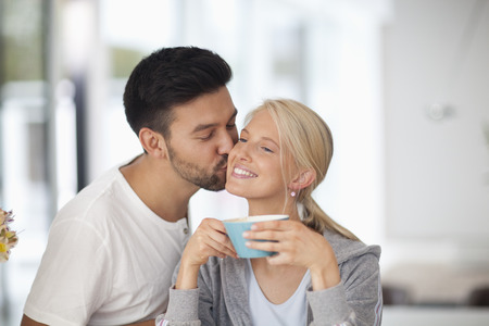 Mid adult man kissing woman holding tea cup