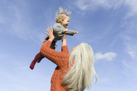 Mature woman playing with granddaughter against blue sky LANG_EVOIMAGES