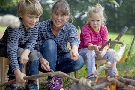 Kindergarten kids preparing campfire bread in a wood kindergarten