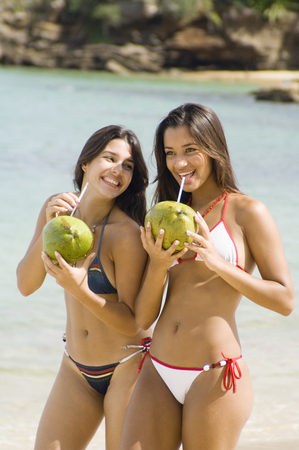 Two women holding coconuts with straws at beach