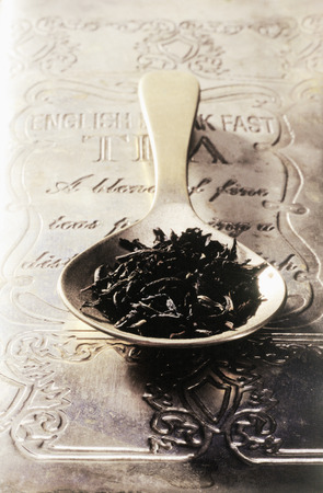 Detail view of a spoon full of tea leaves on top of a metal tea box, English breakfast tea LANG_EVOIMAGES