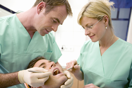 Dentist and assistant treating patient LANG_EVOIMAGES