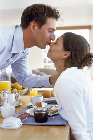 View of couple kissing at the breakfast table