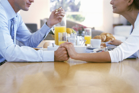 View of a couple holding hands at the breakfast table LANG_EVOIMAGES