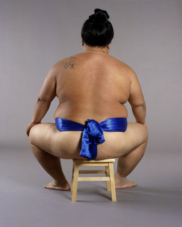 Portrait of a sumo wrestler sitting on a stool