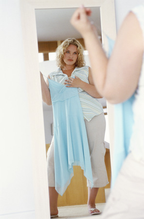 View of overweight woman wishing she could wear smaller clothes