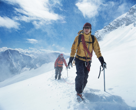 Hikers tied together with safety rope on snowy mountain LANG_EVOIMAGES