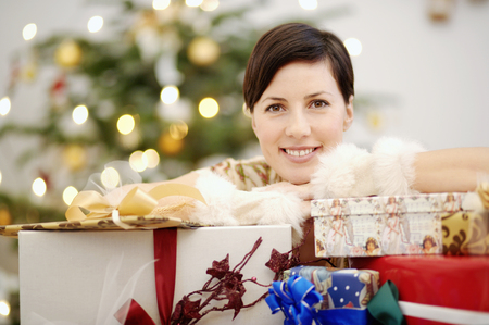 Woman leaning on stack of Christmas gifts LANG_EVOIMAGES