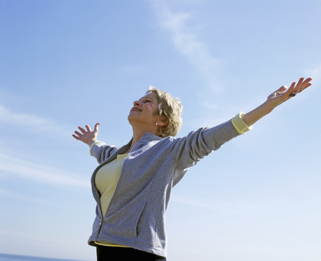 Portrait of a middle aged woman with her arms spread against blue sky LANG_EVOIMAGES