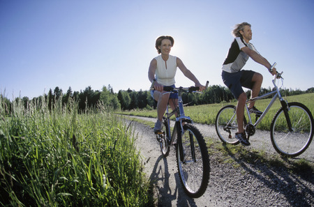 Couple riding bikes on a rural road