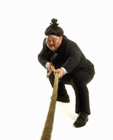 Portrait of a sumo wrestler in a business suit playing tug-of-war