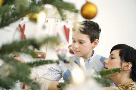 Mother and young son decorating Christmas tree LANG_EVOIMAGES