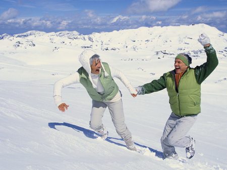 Senior couple holding hands and running in snow LANG_EVOIMAGES